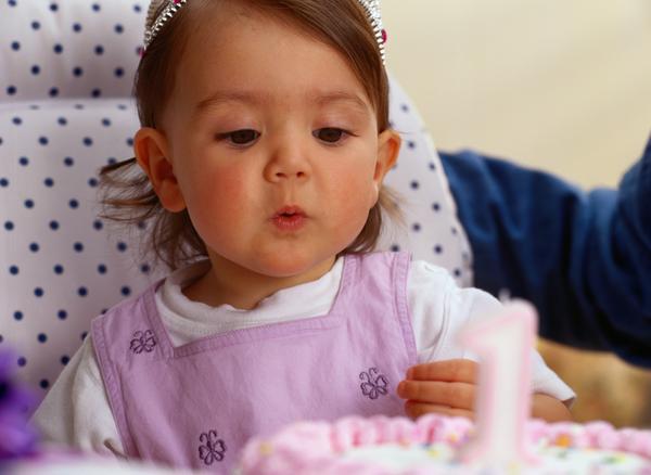 девочка задувает свечку на тортике